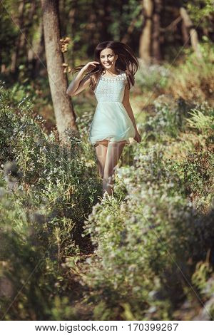 Beautiful young brunette woman running and happy smiling in the blossoming forest meadow on spring. Attractive girl enjoying spring sunny day on the nature