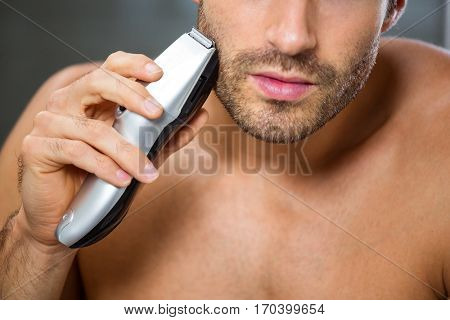 Close-up of young man shaving with trimmer