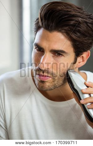 Close-up of smart young man shaving with trimmer