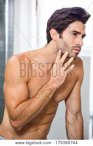 Close-up of young man checking his stubble in bathroom
