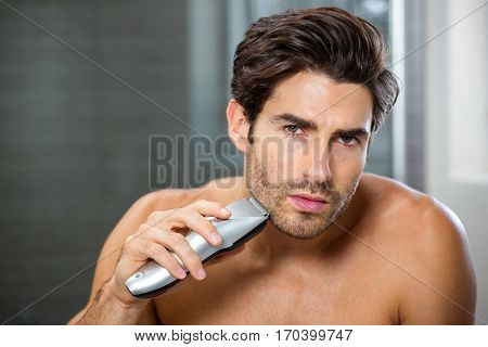 Portrait of young man shaving with trimmer in bathroom