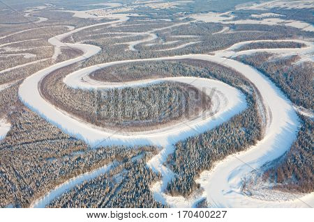 Ugan river in snow covered forest of West Siberia during cold winter day, aerial view.