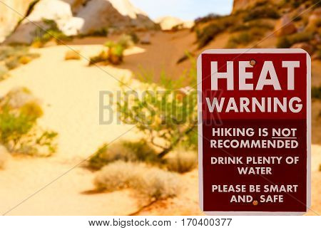 VALLEY OF FIRE USA - JUNE 4 2015: Sign with a Heat Warning. It stands at the White Domes in the Valley of Fire. Hiking ist not recommended. In the background are sand bushes and rocks.