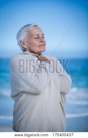 Senior woman relaxing and breathing at the beach