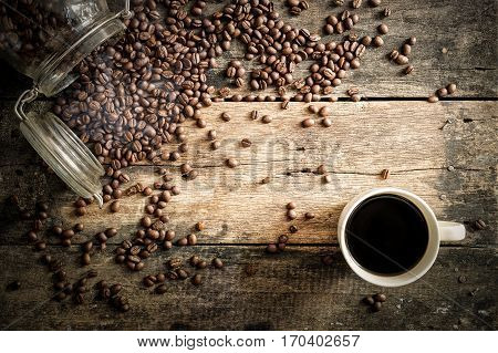 Coffe Beans On The Grunge Wood With Cup Background.