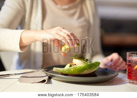 food, new nordic cuisine and people concept - woman eating toast skagen with shrimps, lemon mayonnaise, caviar and buttery bread and squeezing lemon at cafe or restaurant