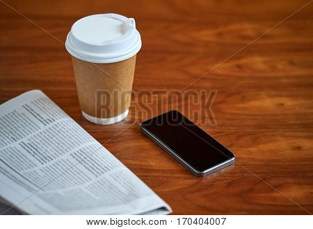 technology, break, mass media and news concept - coffee drink in paper cup, smartphone and newspaper on table