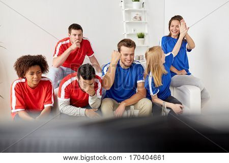 people, leisure, rivalry and sport concept - happy and sad friends or football fans watching soccer game or match at home