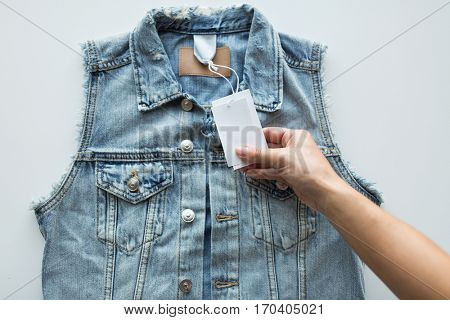 clothes, wear and fashion concept - close up of hand holding price tag of denim waistcoat