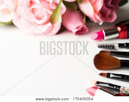 Make up products lipstick, blush and tools brushes with pink roses flowers on white background. Lifestyle woman still life