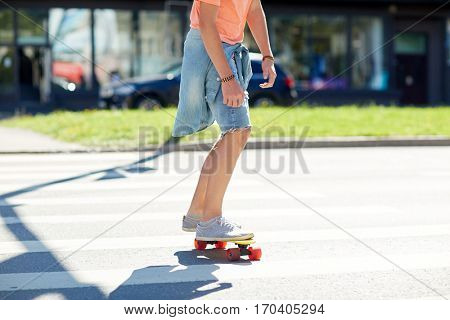 summer, traffic, extreme sport and people concept - teenage boy riding short modern cruiser skateboard on crosswalk in city