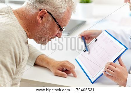 medicine, old age, healthcare, cardiology and people concept - senior man and doctor with cardiogram on clipboard meeting in medical office at hospital
