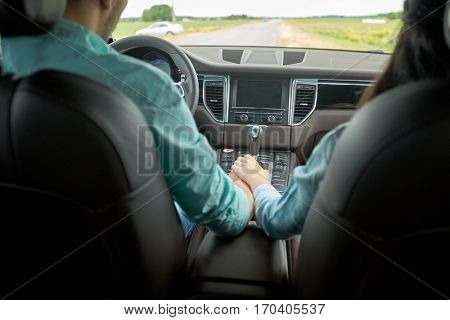 road trip, travel, love and people concept - happy couple driving in car and holding hands