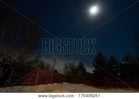 Winter frosty night scene with moon stars and clear sky shot in the yard in the countryside. Tver oblast Russia.