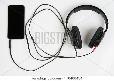 Closed back stereo headphones connected to smart phone on white background
