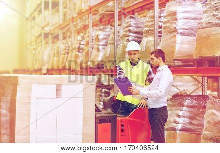 wholesale, logistic, people and export concept - manual worker and businessmen with clipboard at warehouse