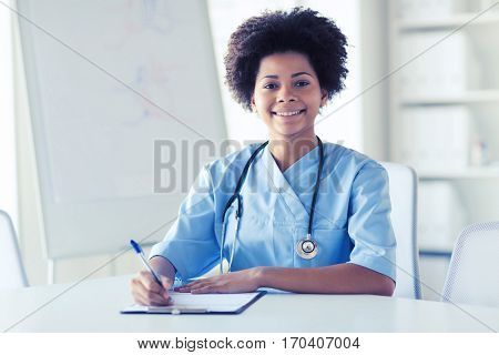 medicine, people and healthcare concept - happy female african american doctor or nurse writing medical report to clipboard at hospital