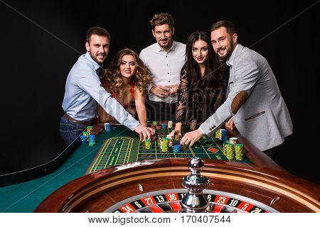 Group of young people behind roulette table on black background. Young people are betting in the game. Players looking to the camera
