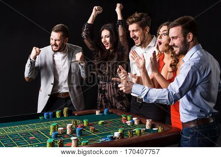 Group of young people behind roulette table on black background. Emotions players