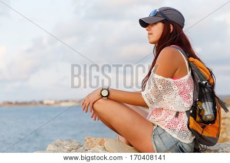 Young girl on sea pier in summer day