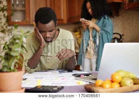 No Money. Young Family In Financial Trouble. Frustrated African Man With Glasses And Pencil In His H