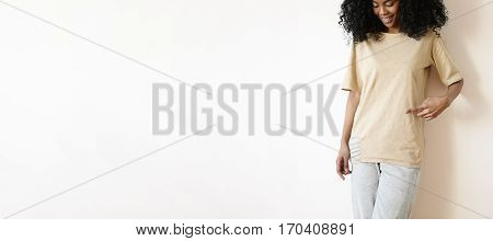 Cropped Shot Of Beautiful Young Dark-skinned Woman With Charming Pretty Smile Posing At Blank White