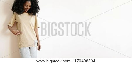 Studio Portrait Of Attractive Young African Female Model With Stylish Curly Haircut Dressed Casually