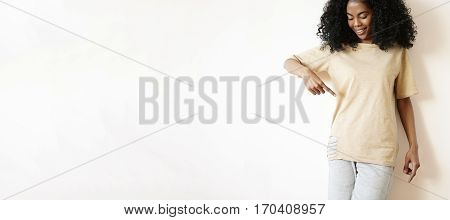 Indoor Shot Of Cheerful Young African Female With Stylish Curly Haircut Wearing Casual Clothes, Look