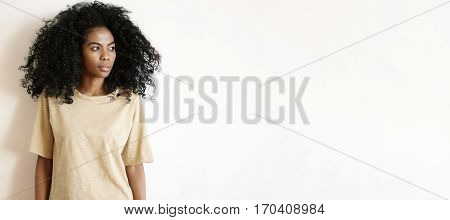 People And Lifestyle. Studio Shot Of Gorgeous African Girl With Afro Hairstyle Wearing Oversize T-sh