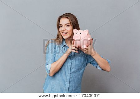 Woman in shirt holding moneybox in hands in studio and looking at camera. Isolated gray background