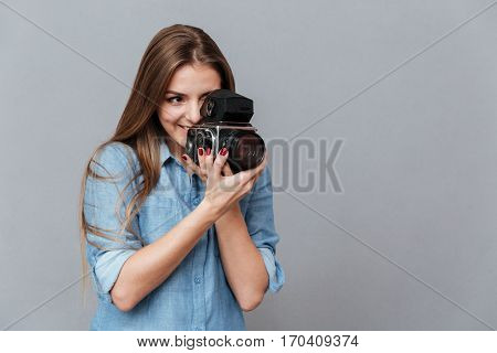 Woman in shirt using retro video camera in studio. Isolated gray background
