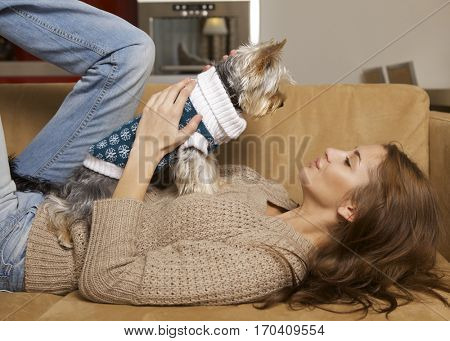 Portrait of young adult attractive brunette girl with her Yorkshire terrier puppy lying on sofa
