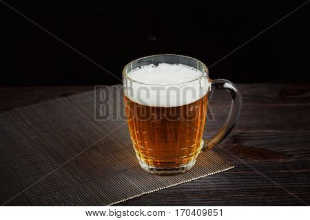 Beer and dried fish on dark wooden table. Beer and beer snack.