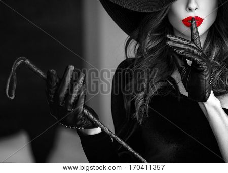 Sexy dominant woman in hat and whip showing no talk closeup bdsm. Selective black and white coloring. Book cover template