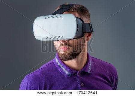 Emotional young man using a VR headset and experiencing virtual reality on grey background. A man dressed in a purple T-shirt