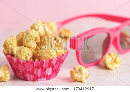 Popcorn and glasses on the table. Paper cup with popcorn