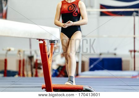 prepare young female athlete gymnast on balance beam