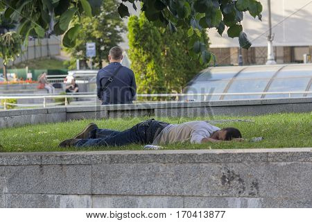 Kiev Ukraine - June 19 2016: Drunk man sleeping on the lawn on the central square. Kiev Ukraine