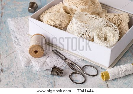Accessories for needlework. Box with lacy ribbons, spools of thread, thimble and scissors on the old wooden table.