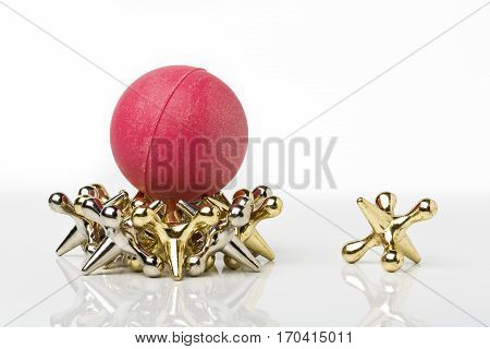 Silver and gold color jacks game pieces with rubber ball.