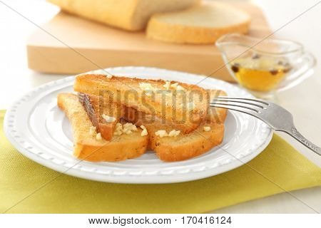 Plate with tasty garlic French bread slices on napkin