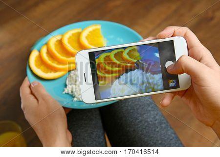Woman taking photo of healthy breakfast, closeup