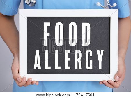 Health care concept. Doctor holding board with text FOOD ALLERGY