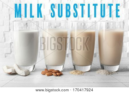 Food substitute concept. Glasses with different milk on white wooden background