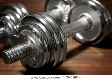 Metal collapsible dumbbells on wooden background, closeup