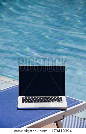 Laptop computer near swimming pool