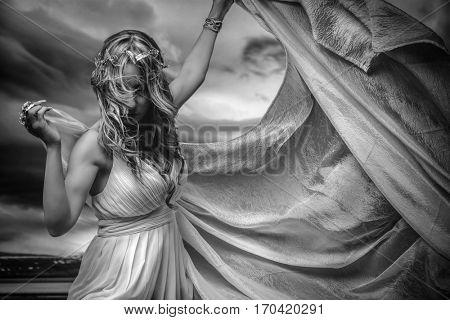 Virgin greek virgin, beautiful blond woman in white silk dress in a romantic or fantasy scene. Jewelry headdress made in silver