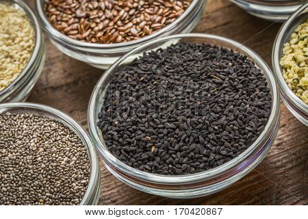 black cumin seeds (Nigella sativa) in a small bowl against rustic barn wood with chia and other healthy seed