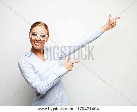 Happy smiling young beautiful business woman showing something or copyspase for product or sign text, over white background