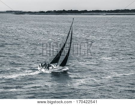 Black and white sailboat navigating through stormy waters